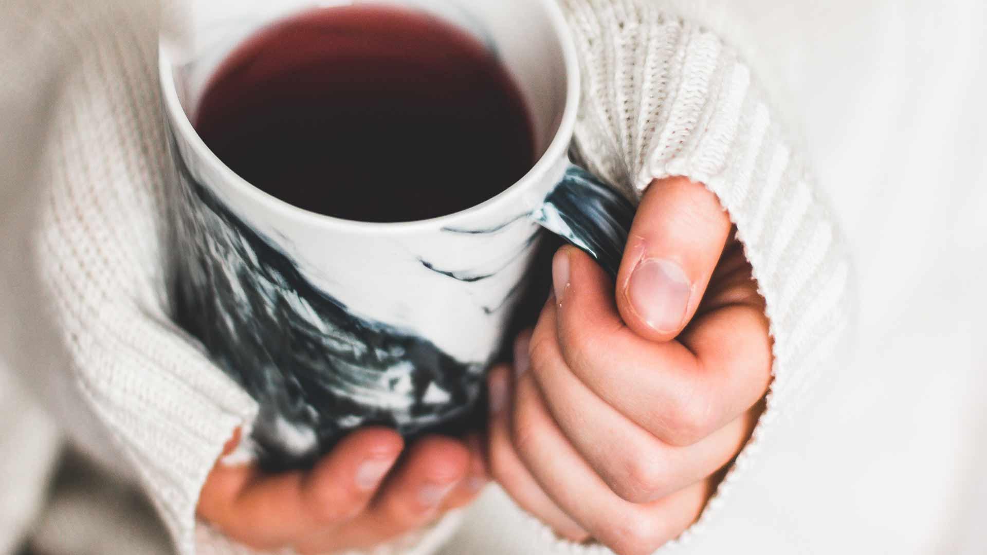 Mulher segura uma xícara de chá para se aquecer