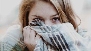 Mulher protegendo o rosto do frio com cachecol