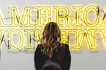 Menina de frente para letreiro luminoso, decidindo onde estudar inglês nos Estados Unidos