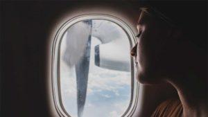 Mulher ao lado da janela do avião